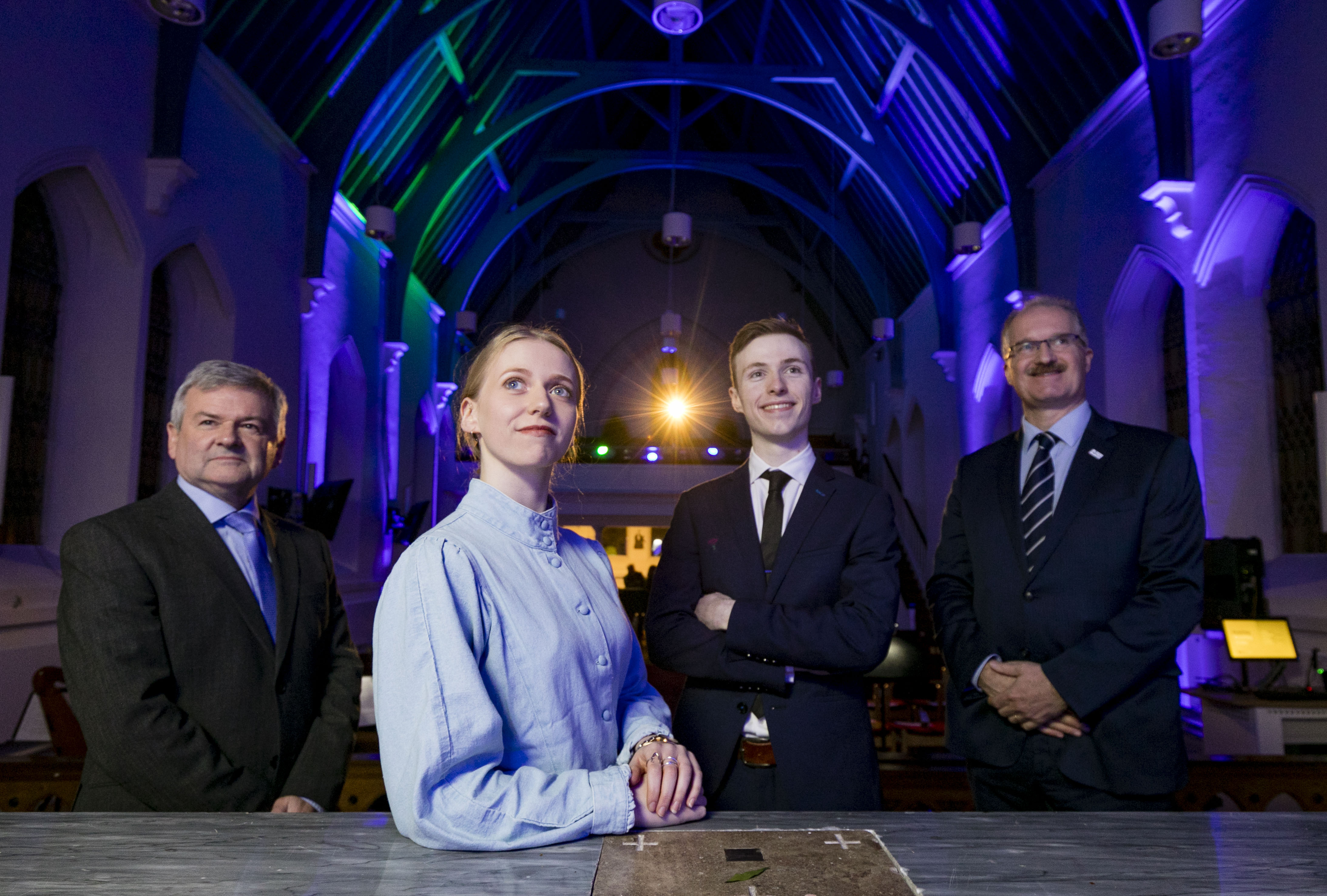 Three men and one woman are smiling and standing in a room in TU Dublin.