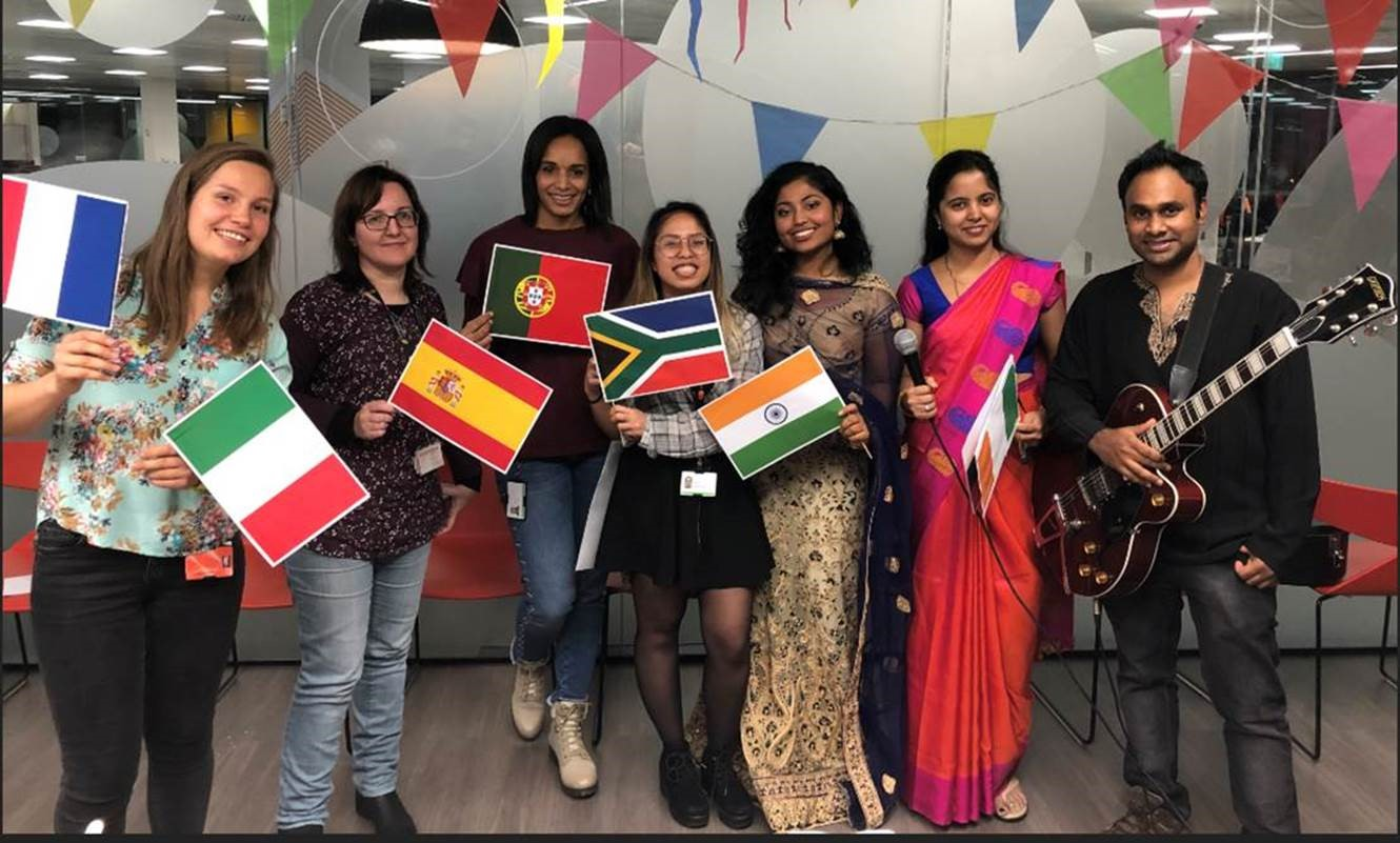 A group of colleagues are smiling into the camera and holding flags of different countries in an office setting.