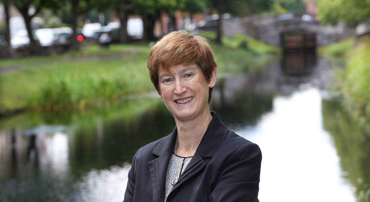 A professional woman is smiling into the camera while standing in front of a canal with trees on its banks in Dublin.