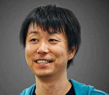 Ryohei Fujimaki of DotData is wearing a blue top and smiling at something off camera in front of a dark grey background.