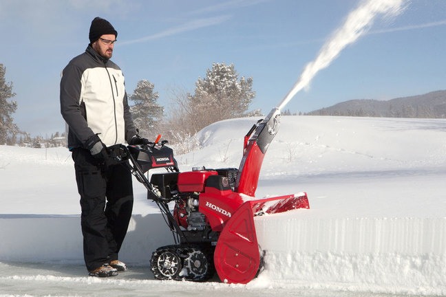 мужчина проводит уборку снега
