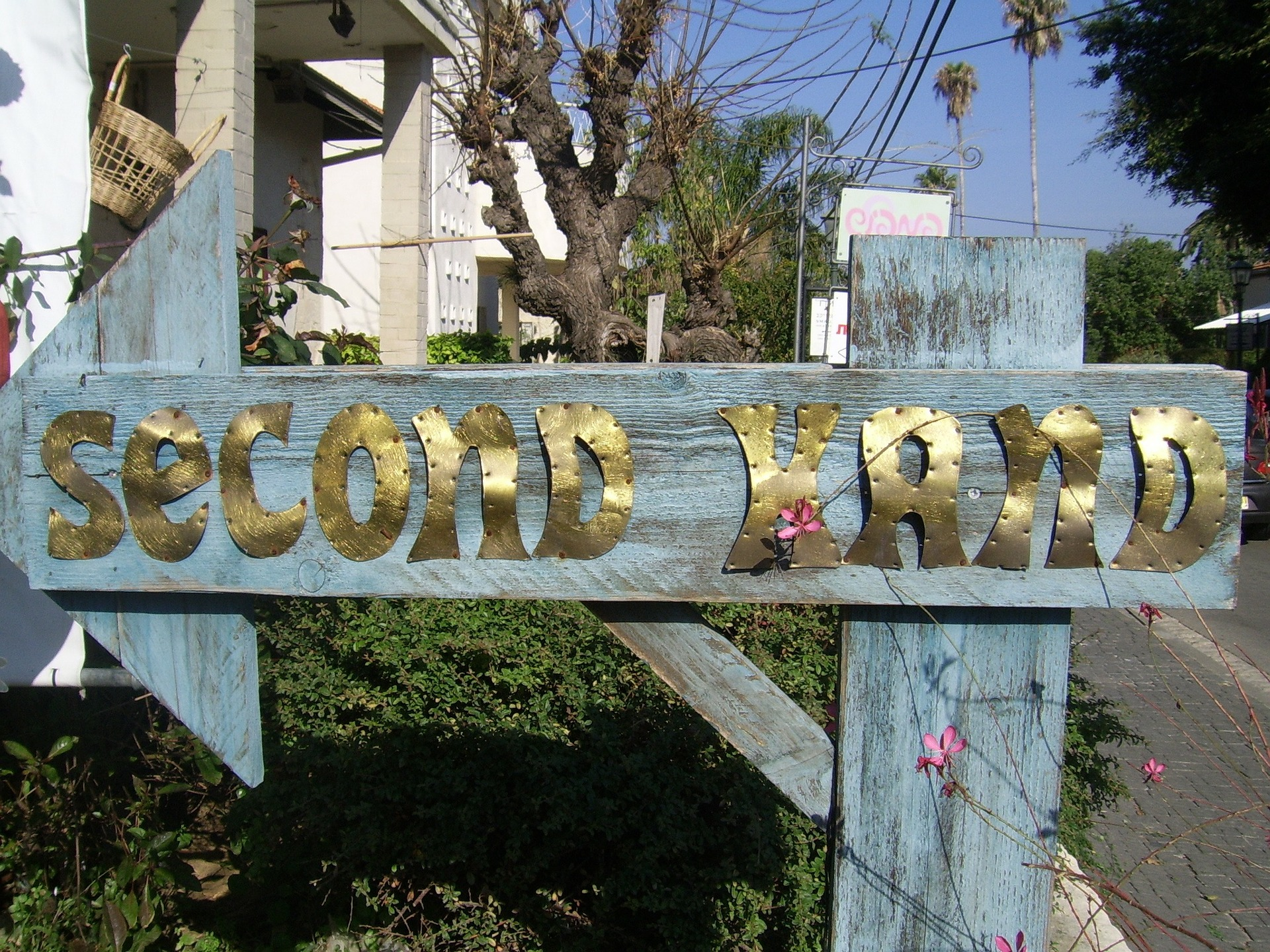 """Large weathered, light blue sign with gold writing saying """"second hand"""" pointing to a thrift store."""