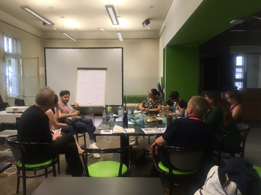 Workshop participants continuing discussions around a table on teaching diversity in HCI