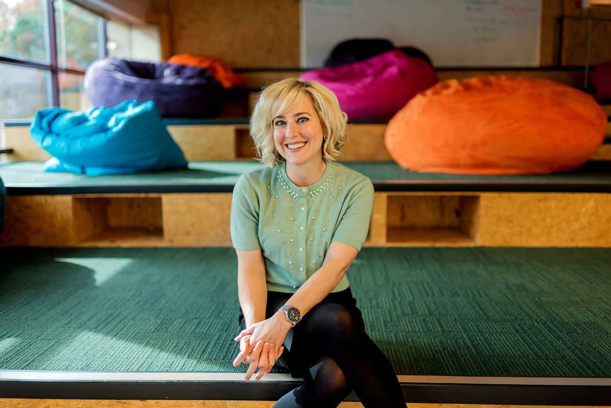 Candace Nicolls is sitting in a colourful room and smiling into the camera.