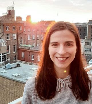 Denise Hensen de Personio est debout à l'extérieur et sourit à la caméra.